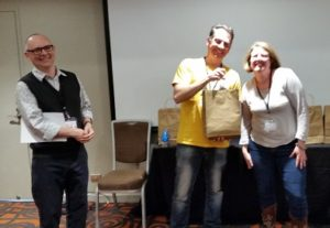 Accepting my winnings at the closing ceremony from MC Sean Williams and convention Chair Leife Shallcross